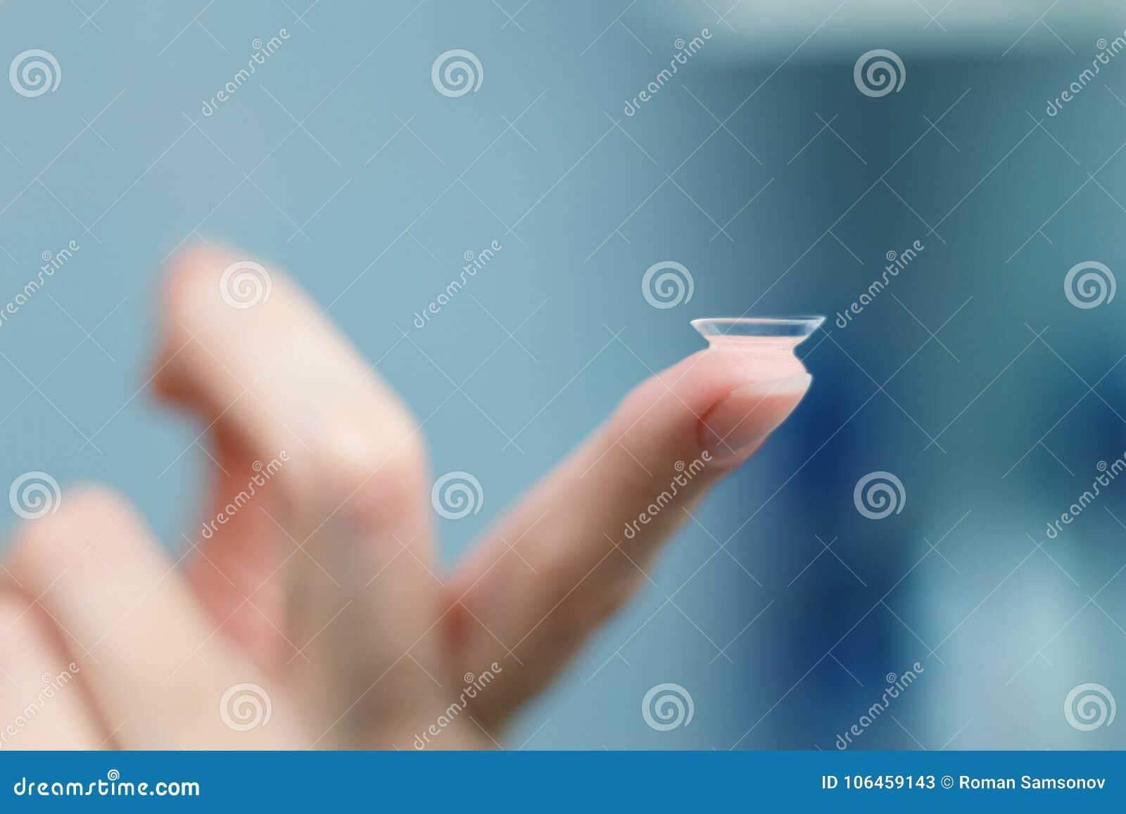 A menina guarda o dedo em uma lente de contato, close up