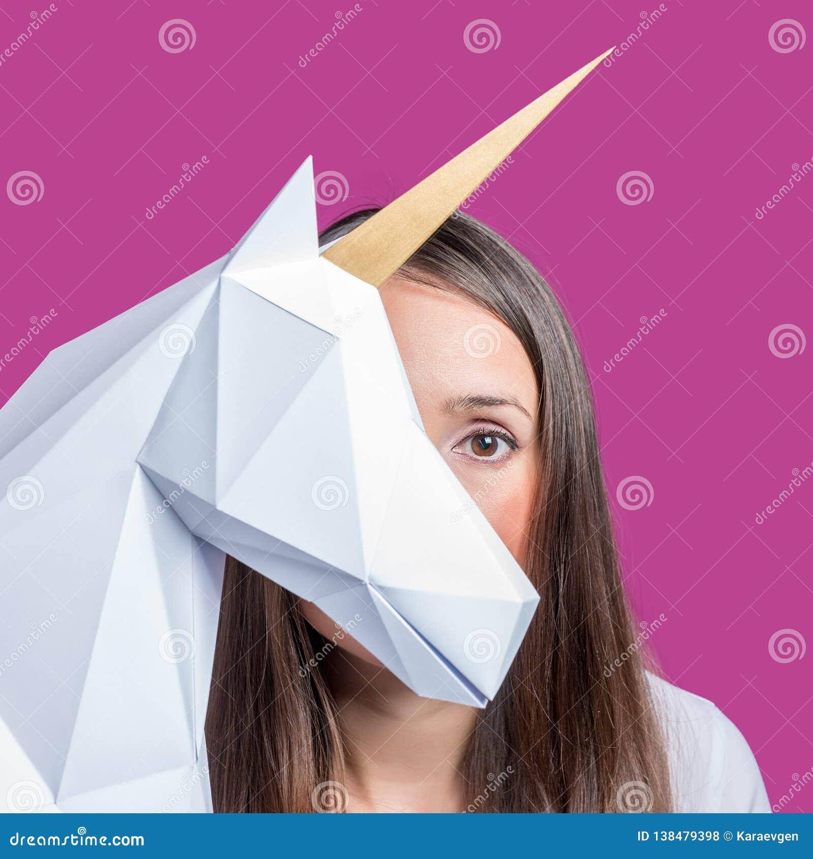 A menina guarda um modelo branco do papercraft 3d do unicórnio Art Concept mínimo