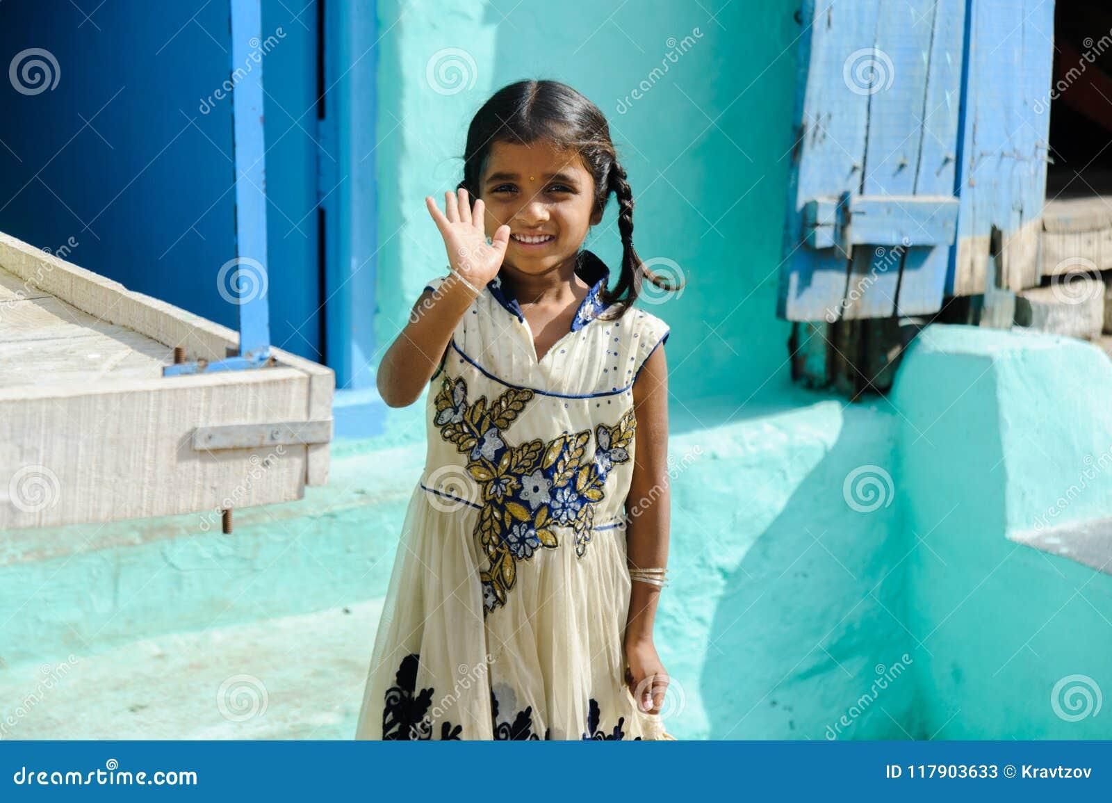 Menina indiana nova que sorri e que acena à mão in camera ar livre no 11 de fevereiro de 2018 Puttaparthi, Índia