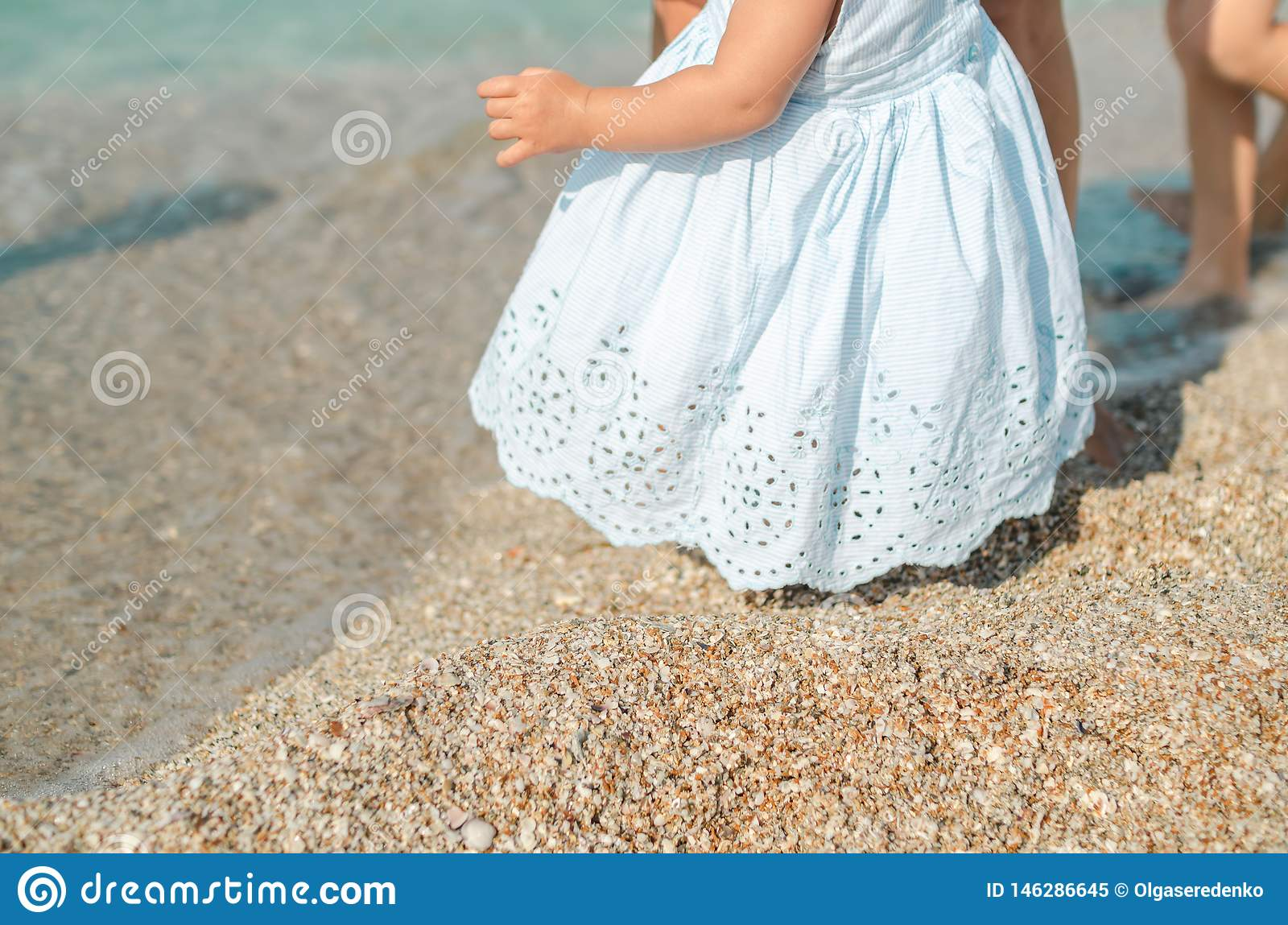 Menina infantil no vestido azul que toma primeiramente etapas na areia com ajuda da mamã na praia ensolarada