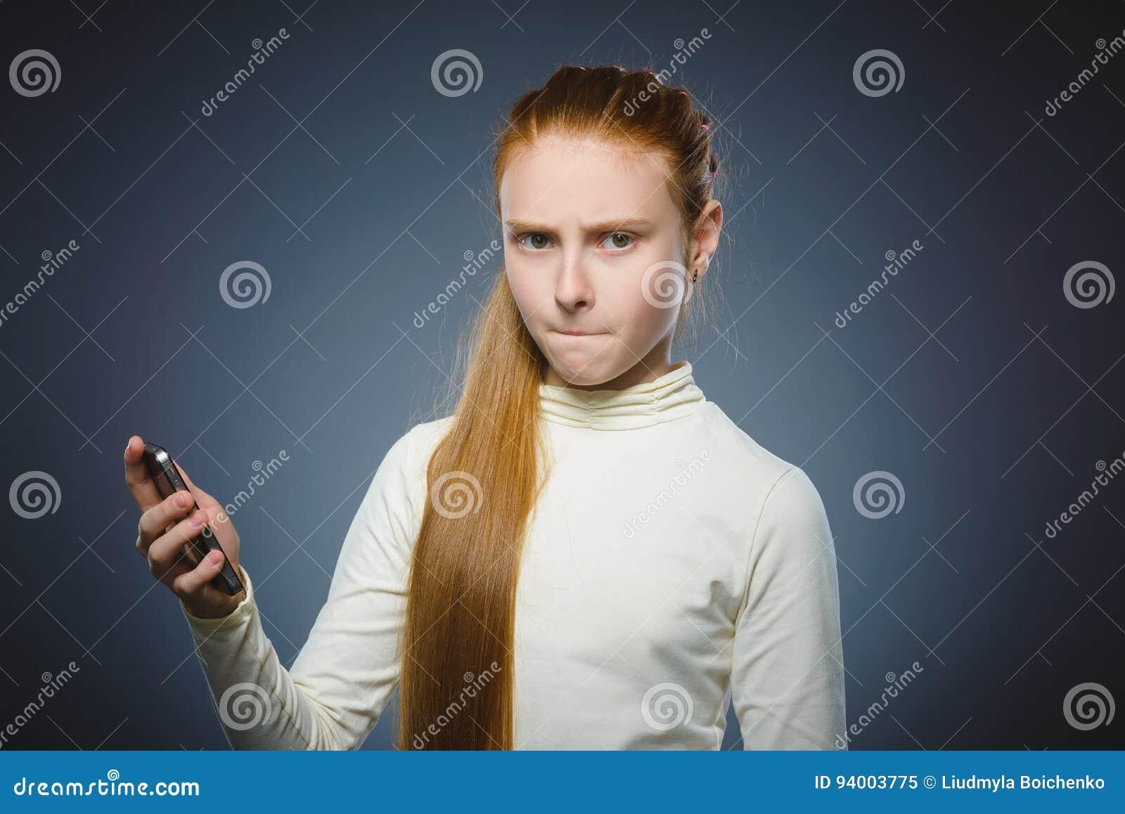 Menina irritada do ruivo com telefone celular Isolado no cinza