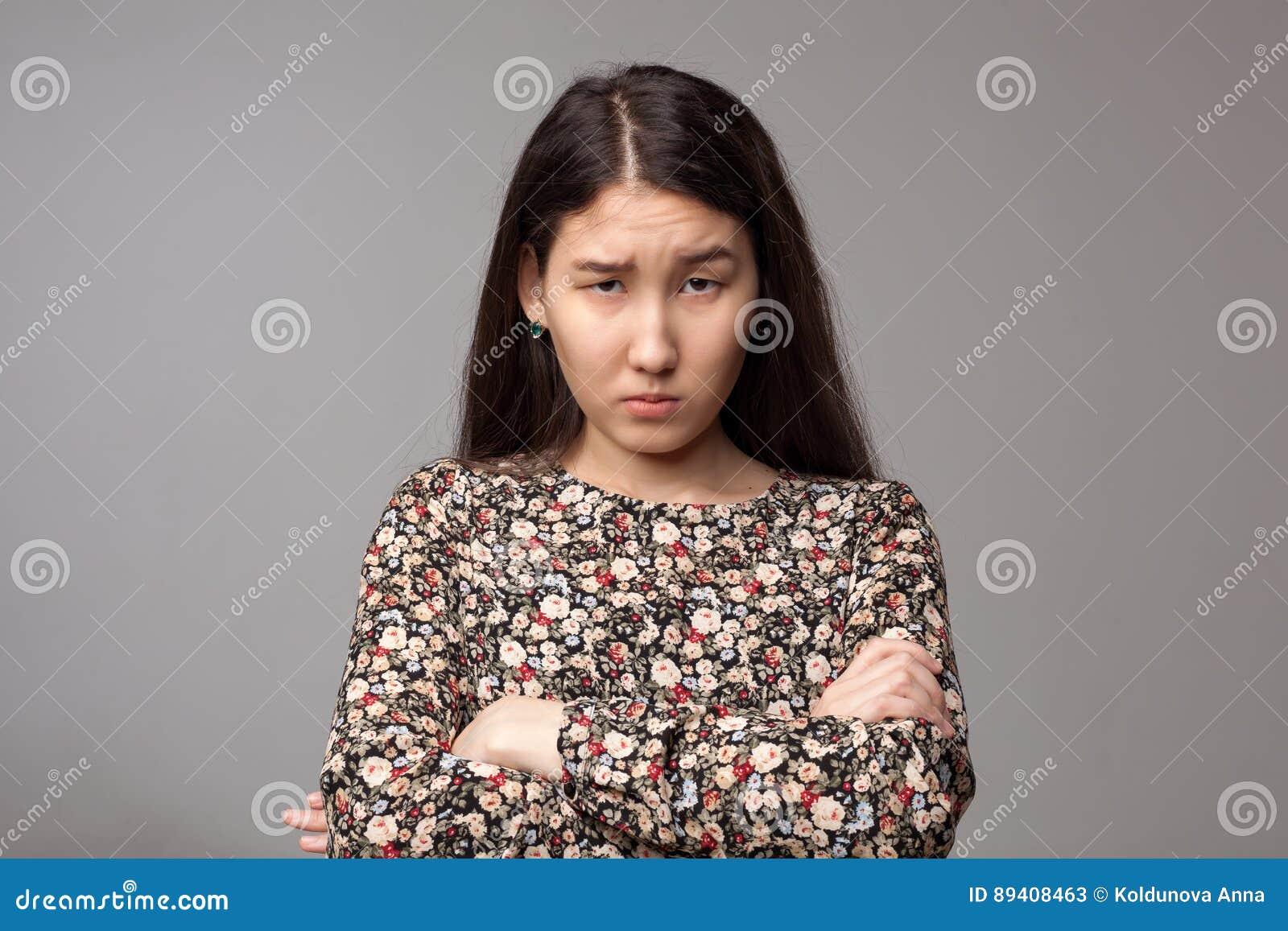 A menina irritada olha de sobrancelhas franzidas cara