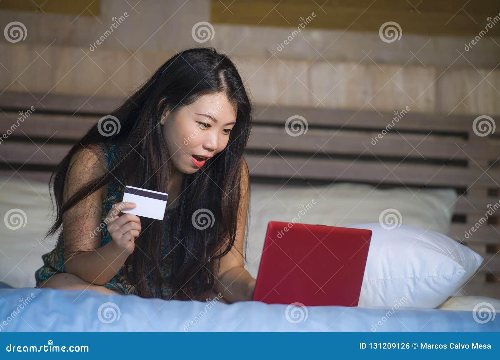 Menina japonesa asiática feliz bonita nova que usa Internet banking do cartão de crédito no laptop em casa na compra E.C. em linh