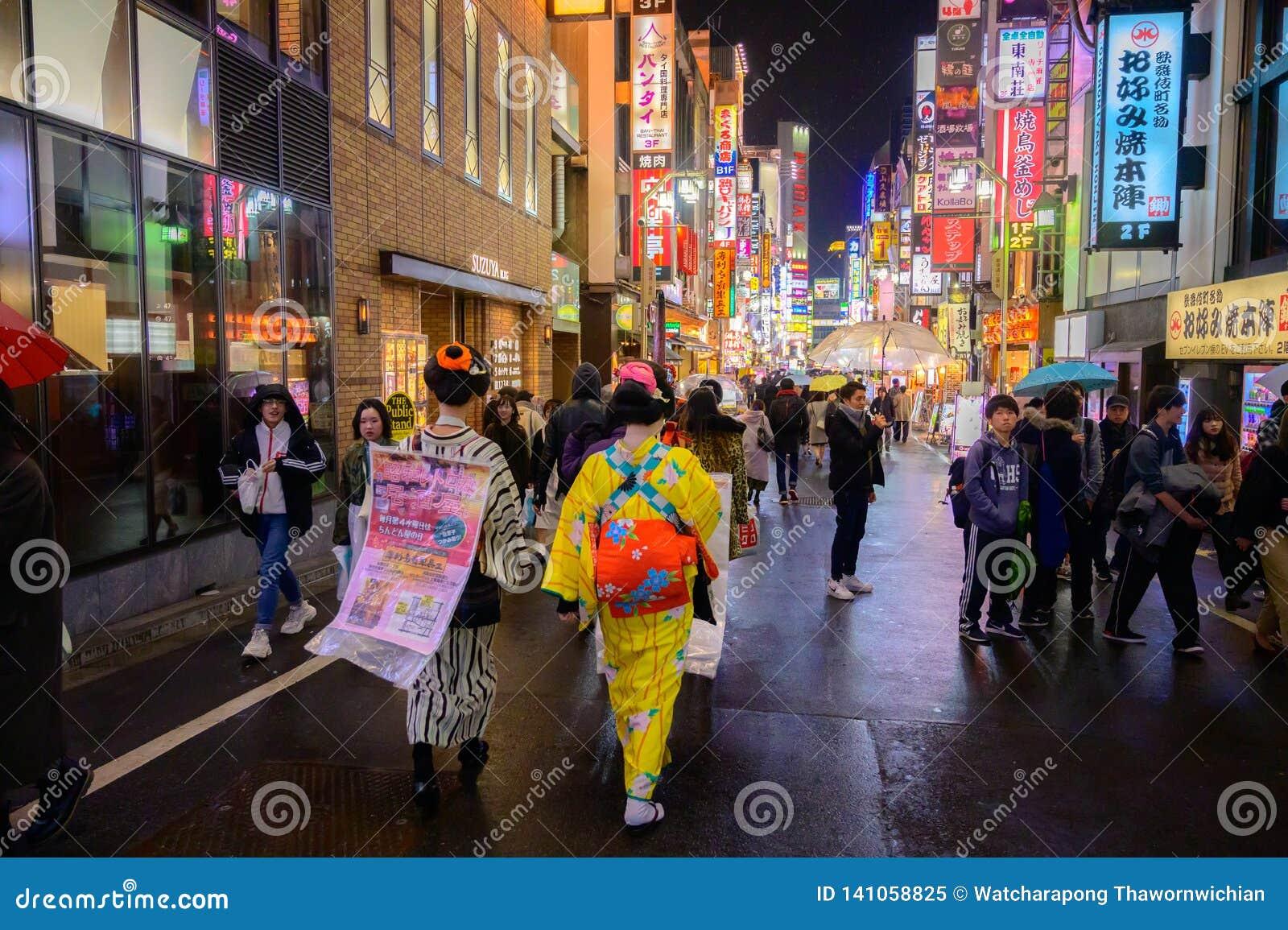 Menina japonesa na caminhada do vestido de Gimono no shopping famoso mesmo do Tóquio, do Japão de Shinjuku Kabukicho, entretenime