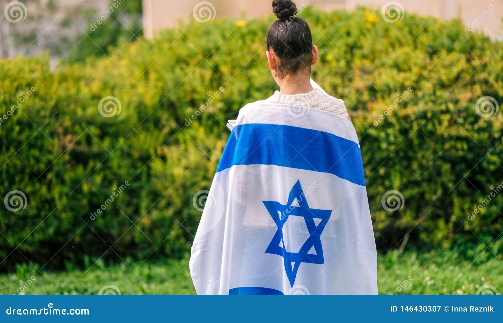 Menina judaica da vista traseira com a bandeira israelita envolvida em torno dela