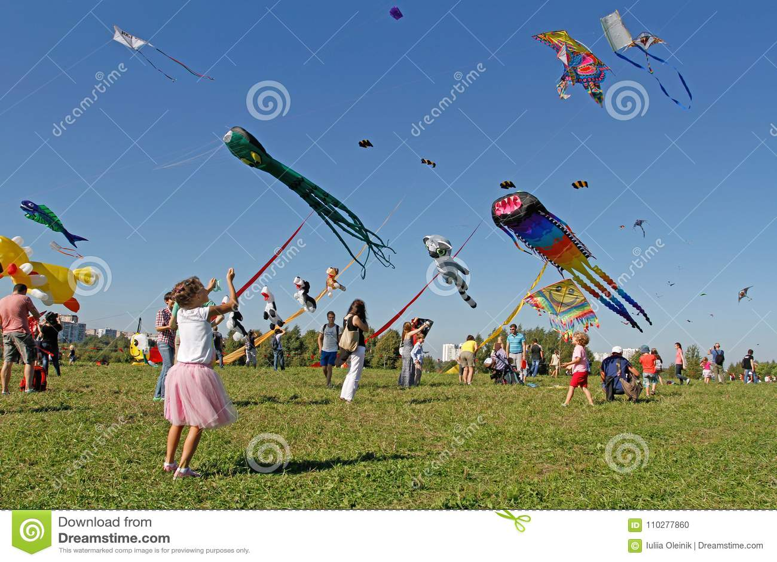 A menina lança um papagaio no céu no festival do papagaio no parque Tsaritsyno em Moscou