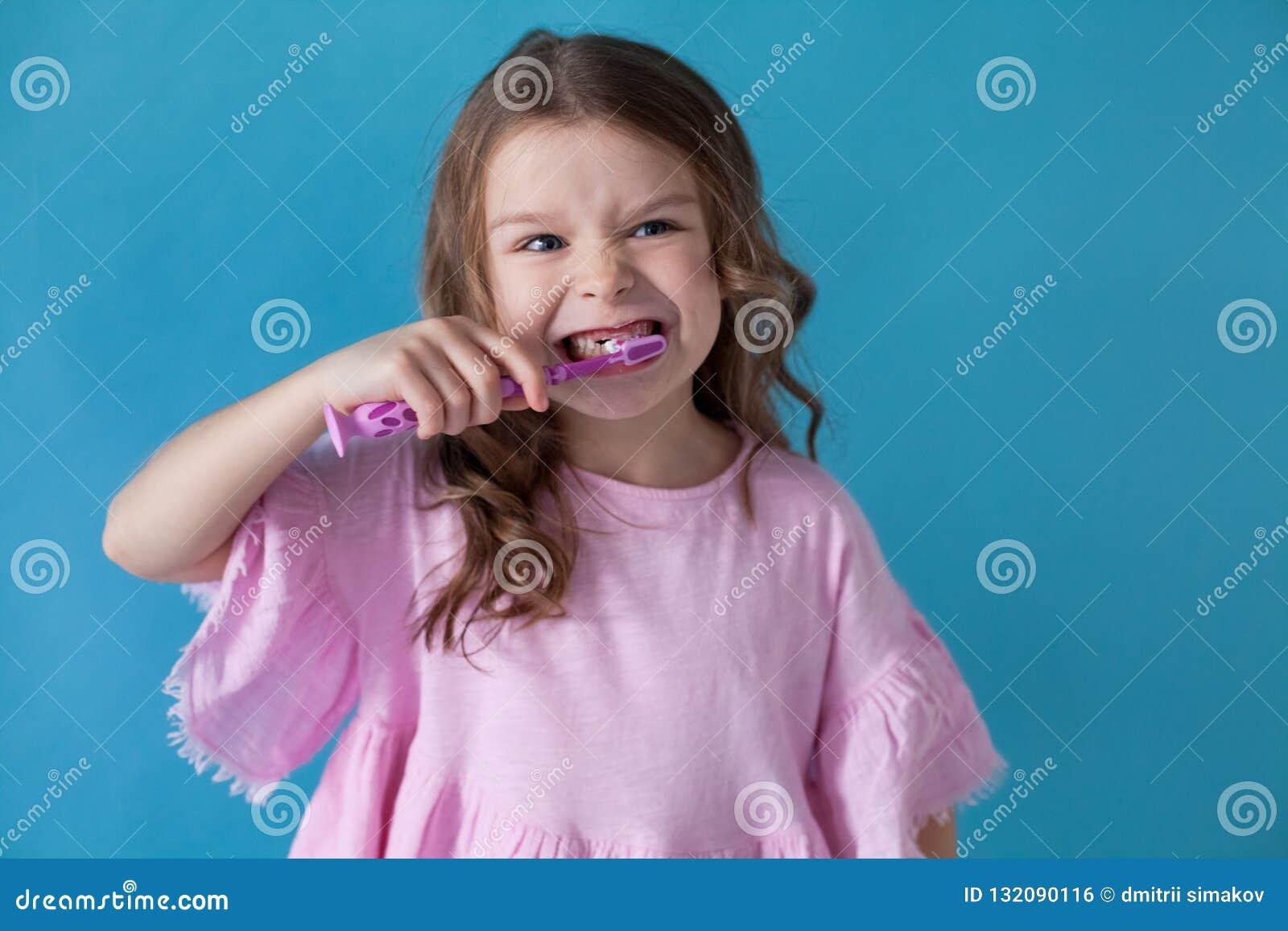 A menina limpa os cuidados médicos da odontologia dos dentes agradáveis