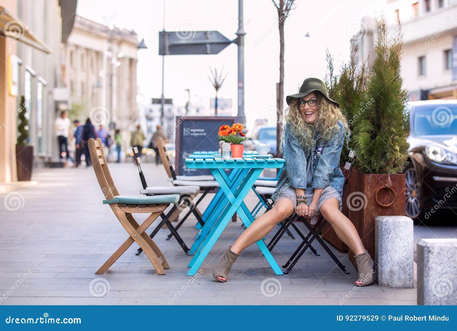 Menina louca na tabela que bebe uma xícara de café na cidade