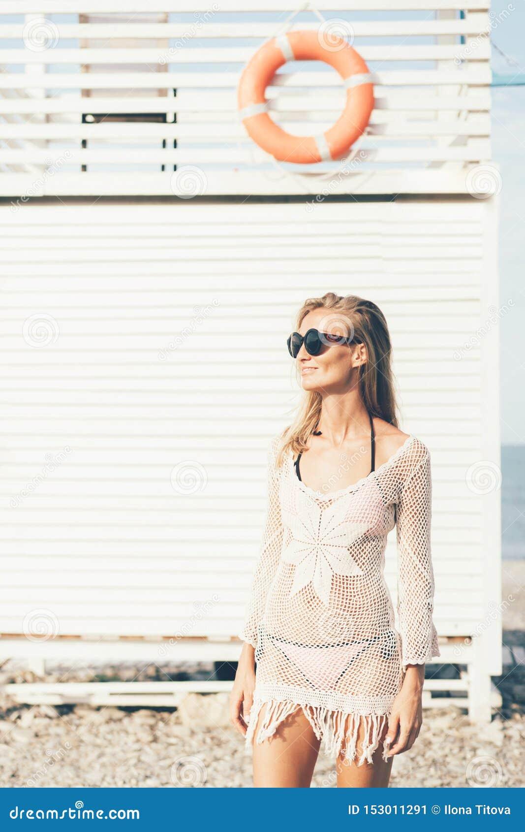 Menina loura à moda em um roupa de banho e em um vestido do verão na praia na perspectiva de uma torre de madeira do salvamento v