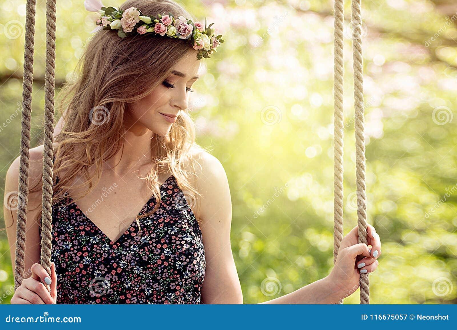 Menina loura atrativa no jardim de florescência