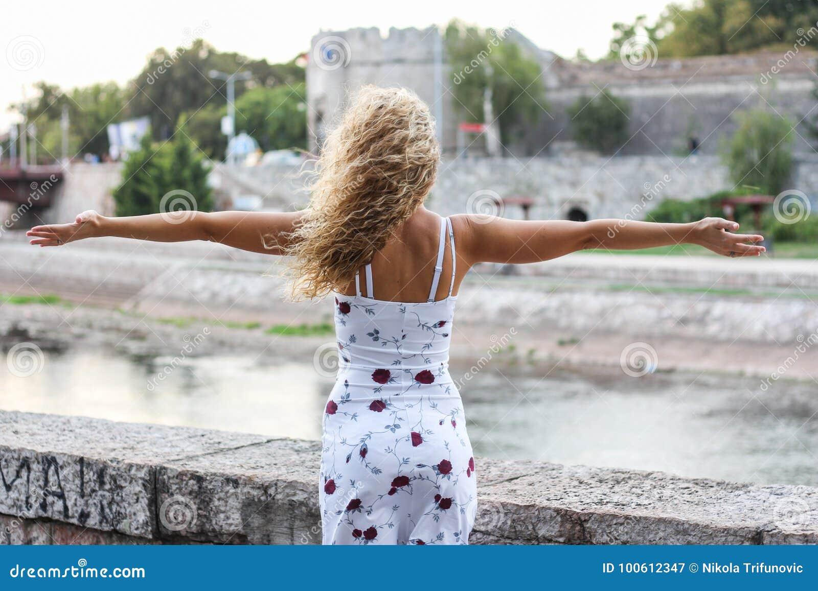 Menina loura atrativa nova que espalha seus braços