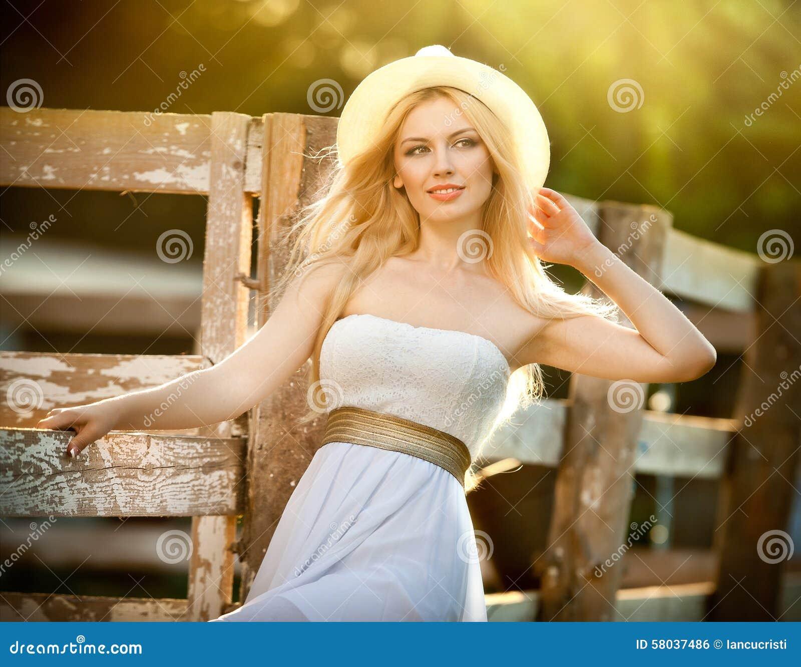 Menina loura bonita com olhar do país perto de uma cerca de madeira velha no dia de verão ensolarado