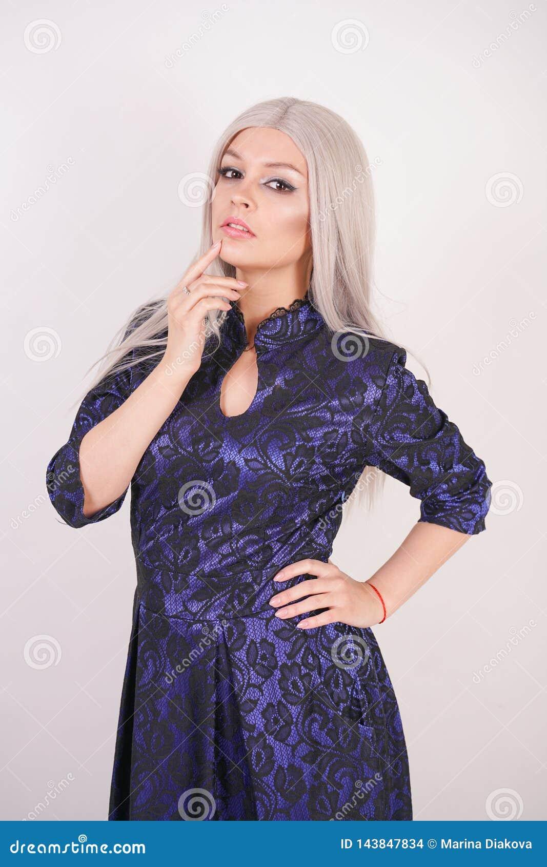 Menina loura bonita no azul luxuoso com o vestido de noite preto do laço no fundo branco no estúdio
