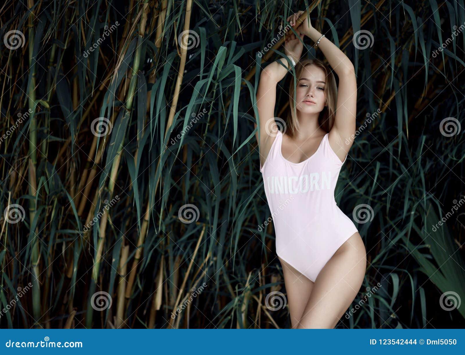 Menina loura bonita nova que levanta no recurso de bambu tropical da floresta na veste  sexy  do corpo do sinal cor-de-rosa do un