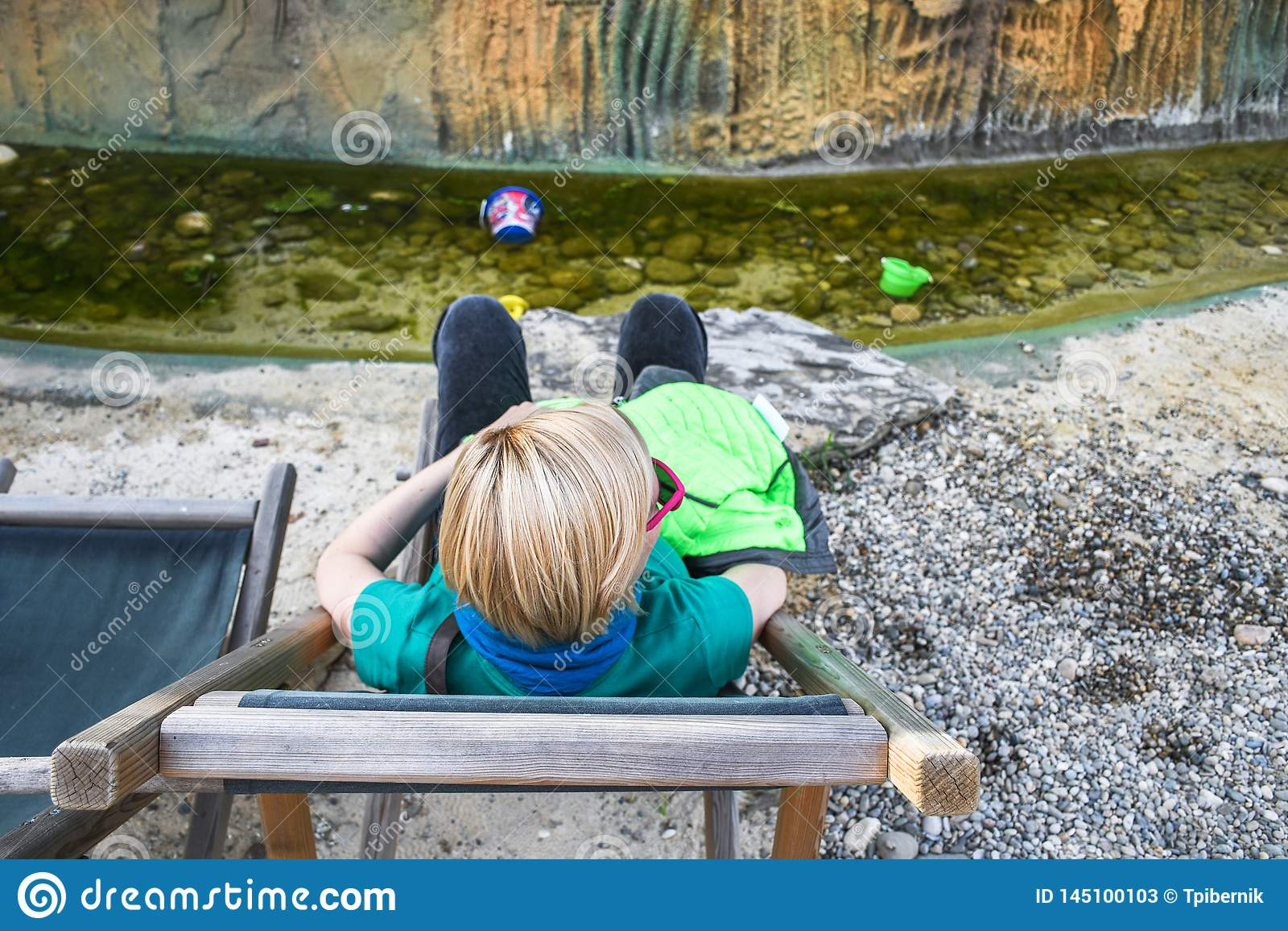 Menina loura bonito com os óculos de sol cor-de-rosa que sentam-se e que descansam em uma cadeira de plataforma e que relaxam