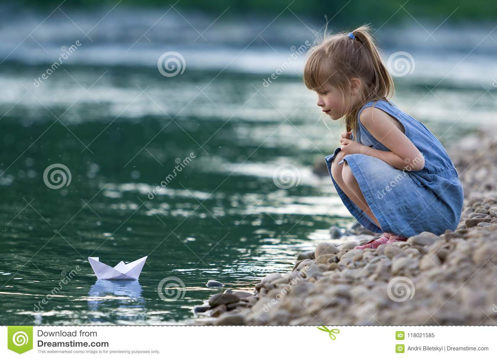 Menina loura bonito pequena adorável no vestido azul no pebbl do riverbank