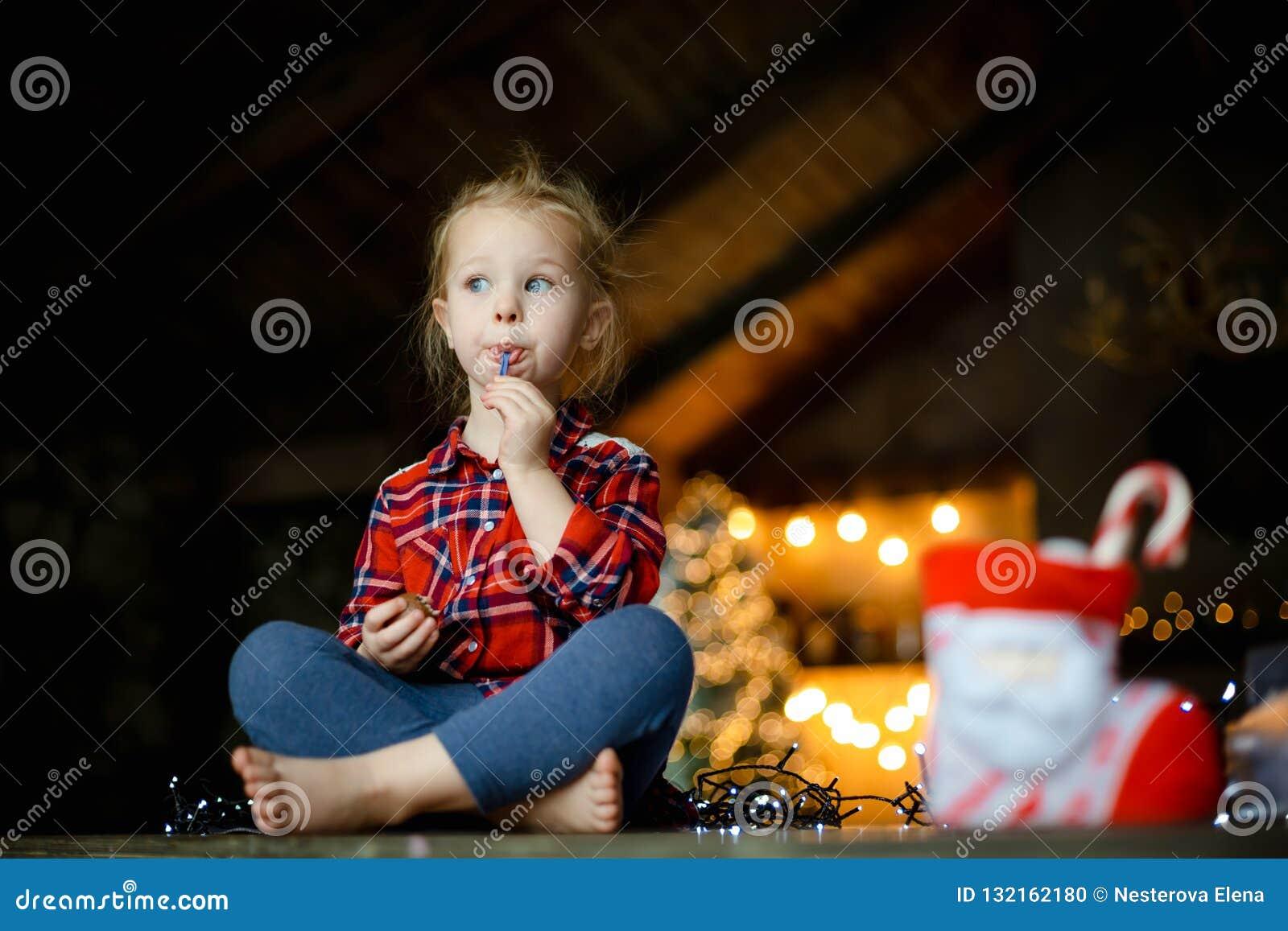 Menina loura branca pequena que senta-se em uma tabela de madeira na sala de visitas do chalé, decorada para a sagacidade da árvo
