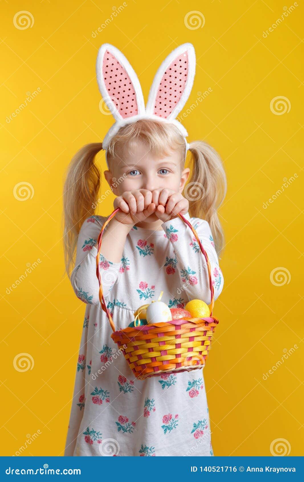 Menina loura caucasiano no vestido branco com as orelhas cor-de-rosa do coelhinho da Páscoa