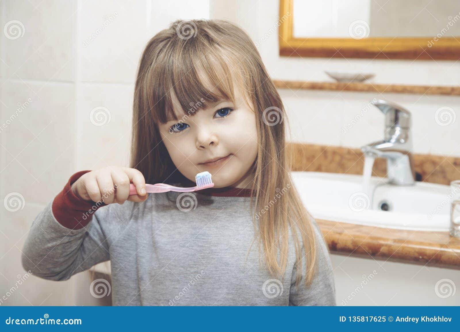 Menina loura com cintas que sorri ao escovar seus dentes