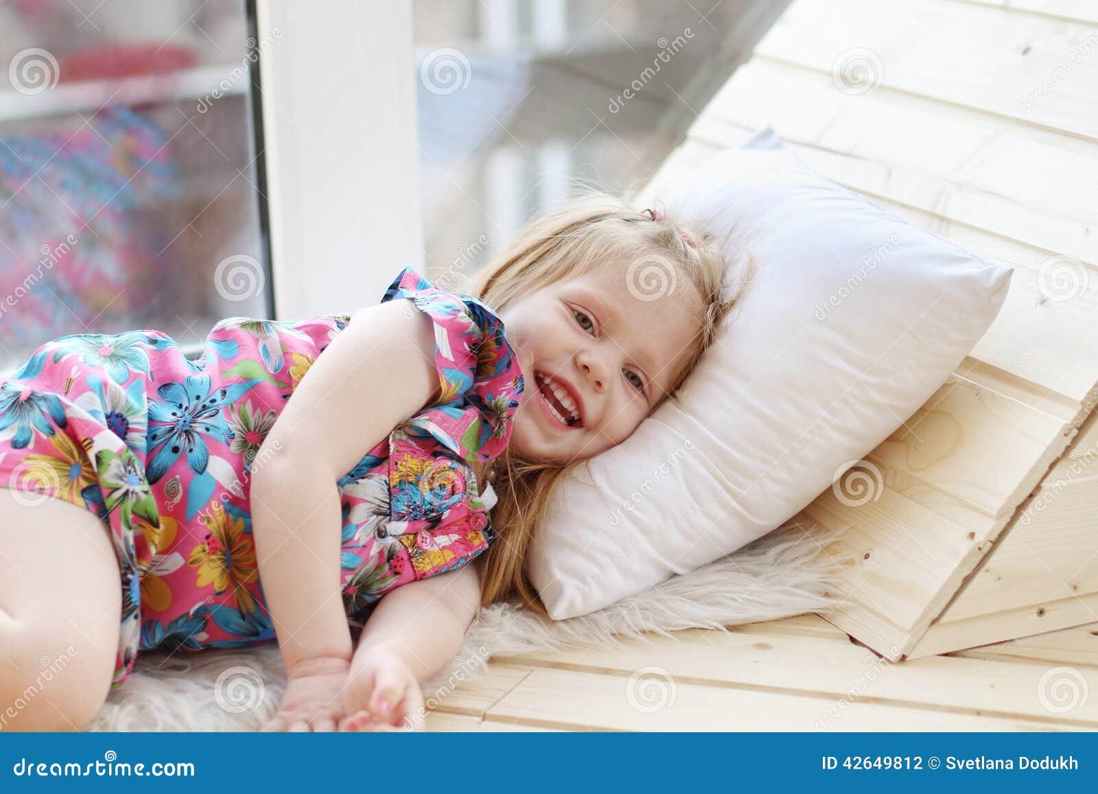 A menina loura consideravelmente pequena ri e encontra-se no descanso branco