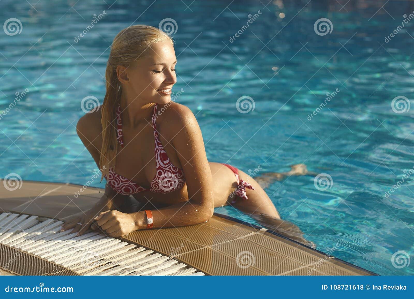 Menina loura elegante e  sexy  bonita na pose do biquini na piscina