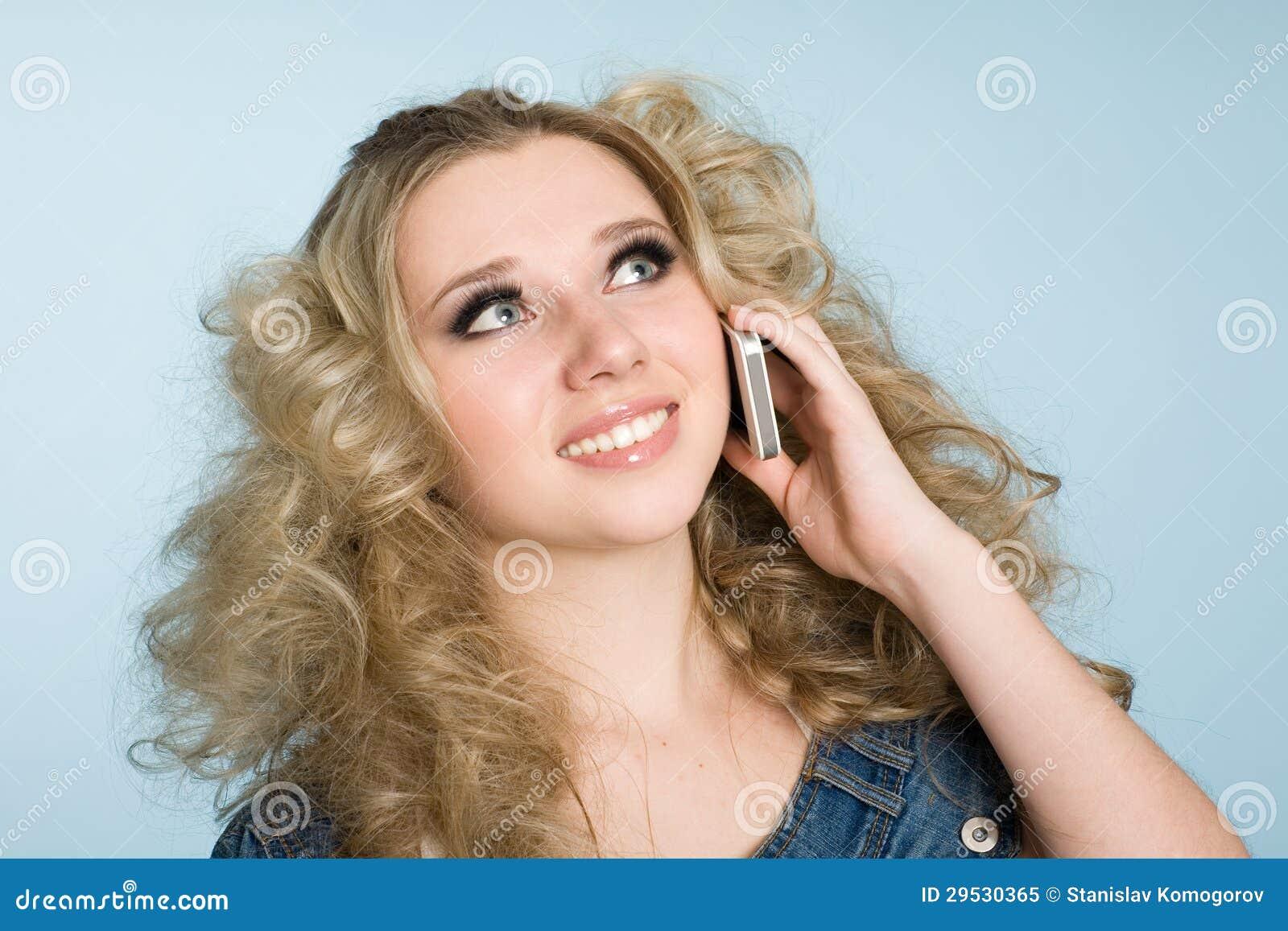 A menina loura está chamando com um telefone móvel.