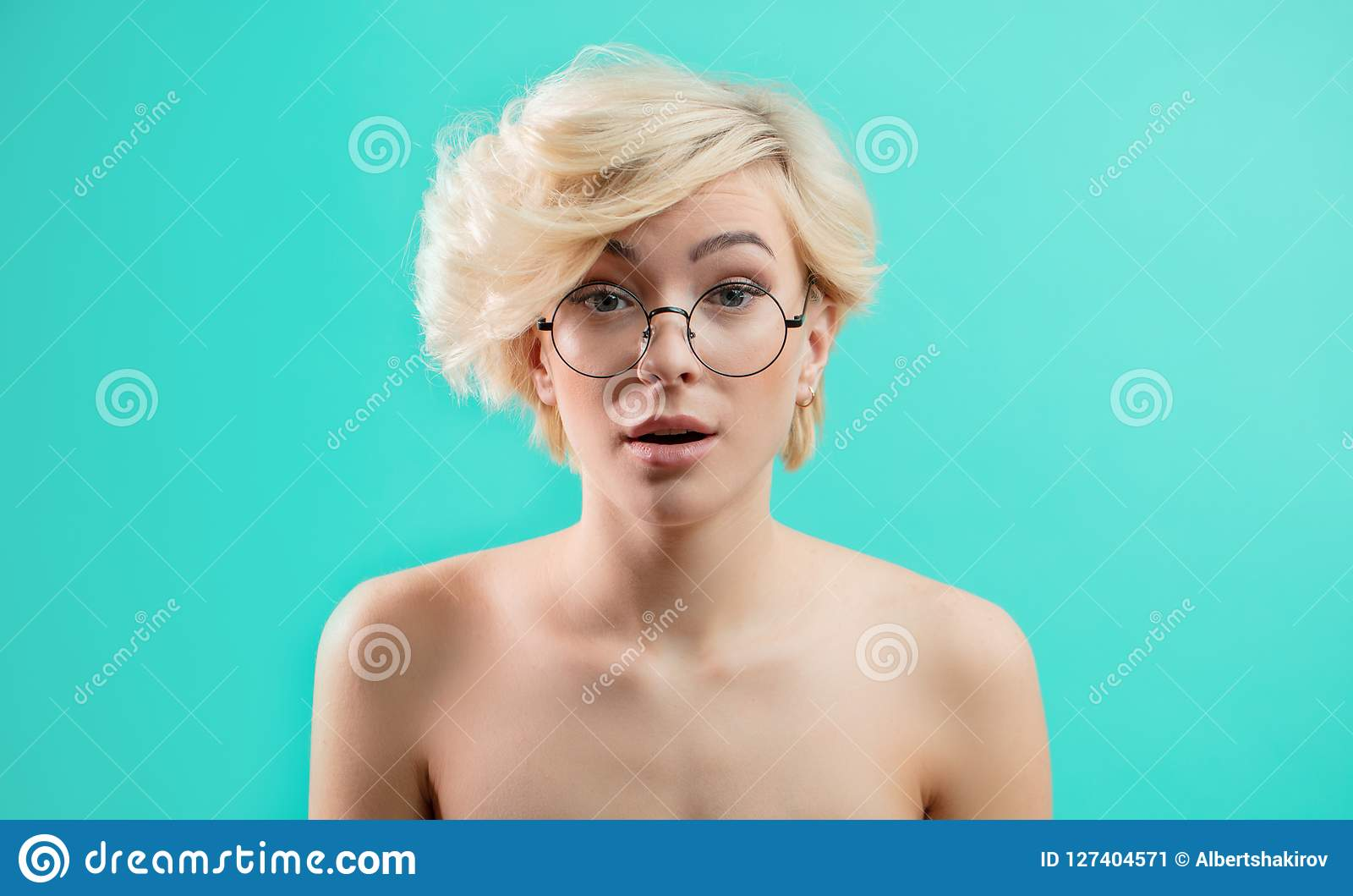 A menina loura impressionante nos vidros olha surpreendida