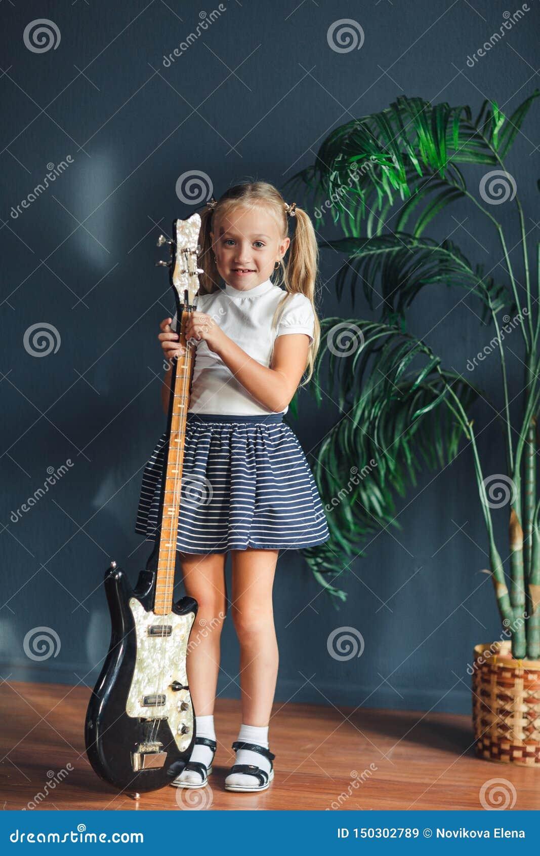 Menina loura nova com as caudas no t-shirt, na saia e nas sandálias brancos com guitarra elétrica em casa