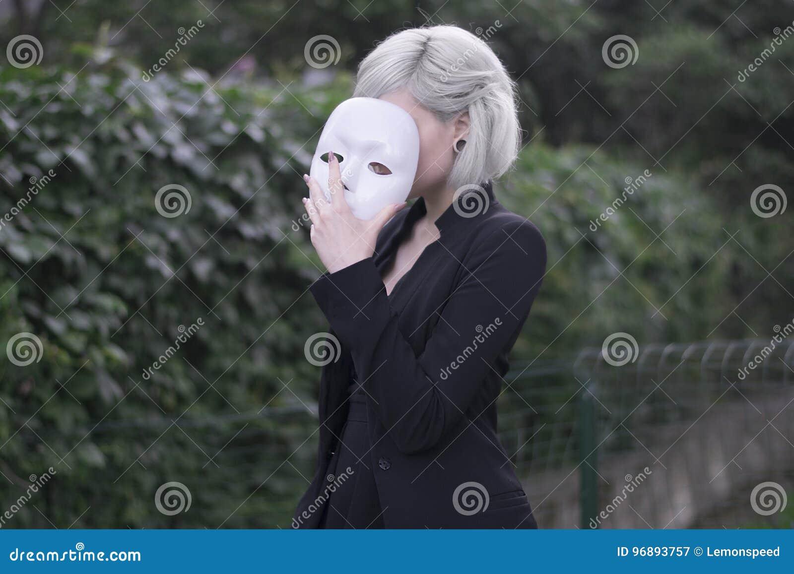 Menina loura nova que descola uma máscara Fingimento ser alguma outra pessoa conceito outdoors