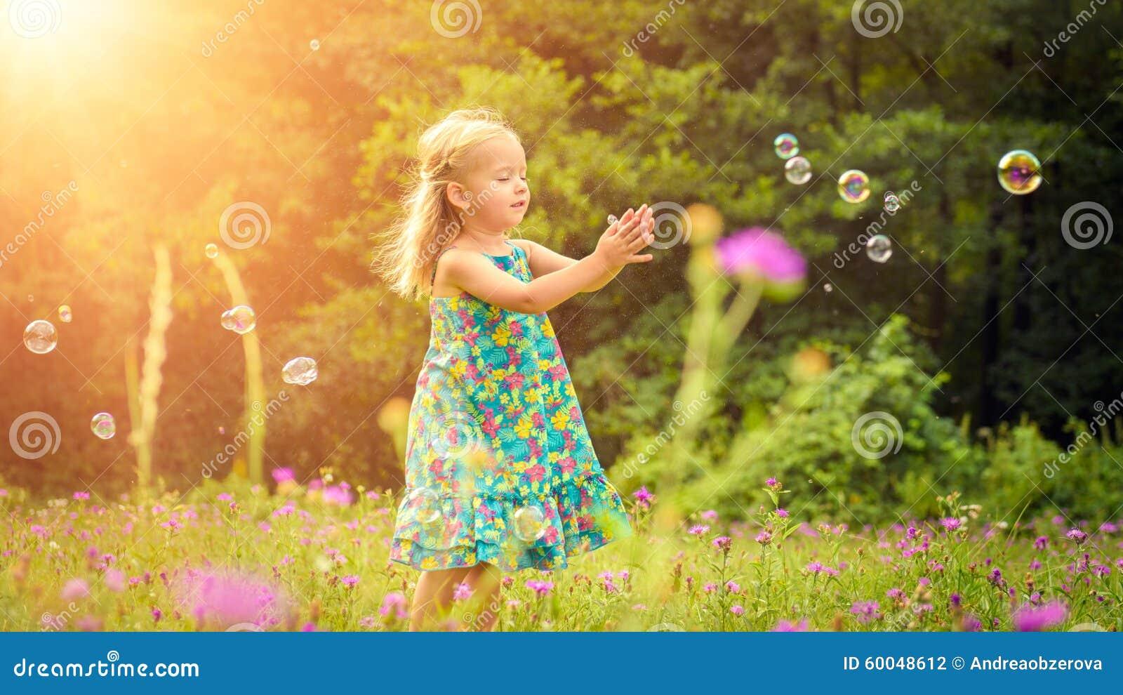 Menina loura pequena adorável que tem o divertimento que joga com bolhas de sabão