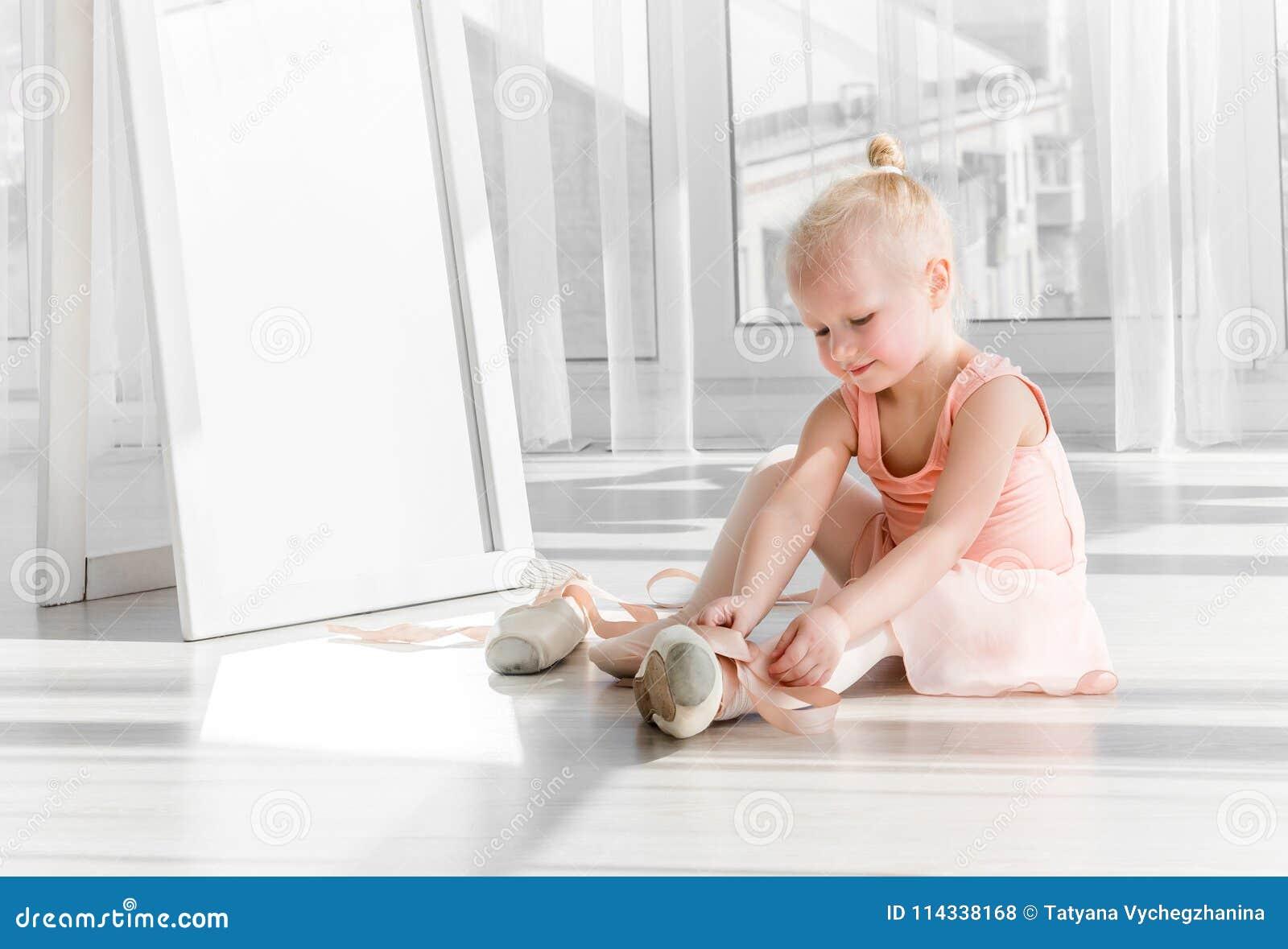 Menina loura pequena bonito que senta-se no assoalho e que amarra sapatas de bailado