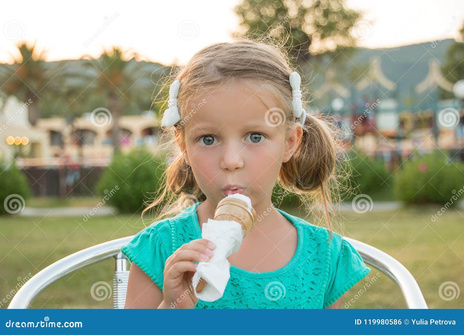 Menina loura pequena doce no t-shirt verde que come seu gelado na luz do sol do verão Férias de verão, sobremesa doce