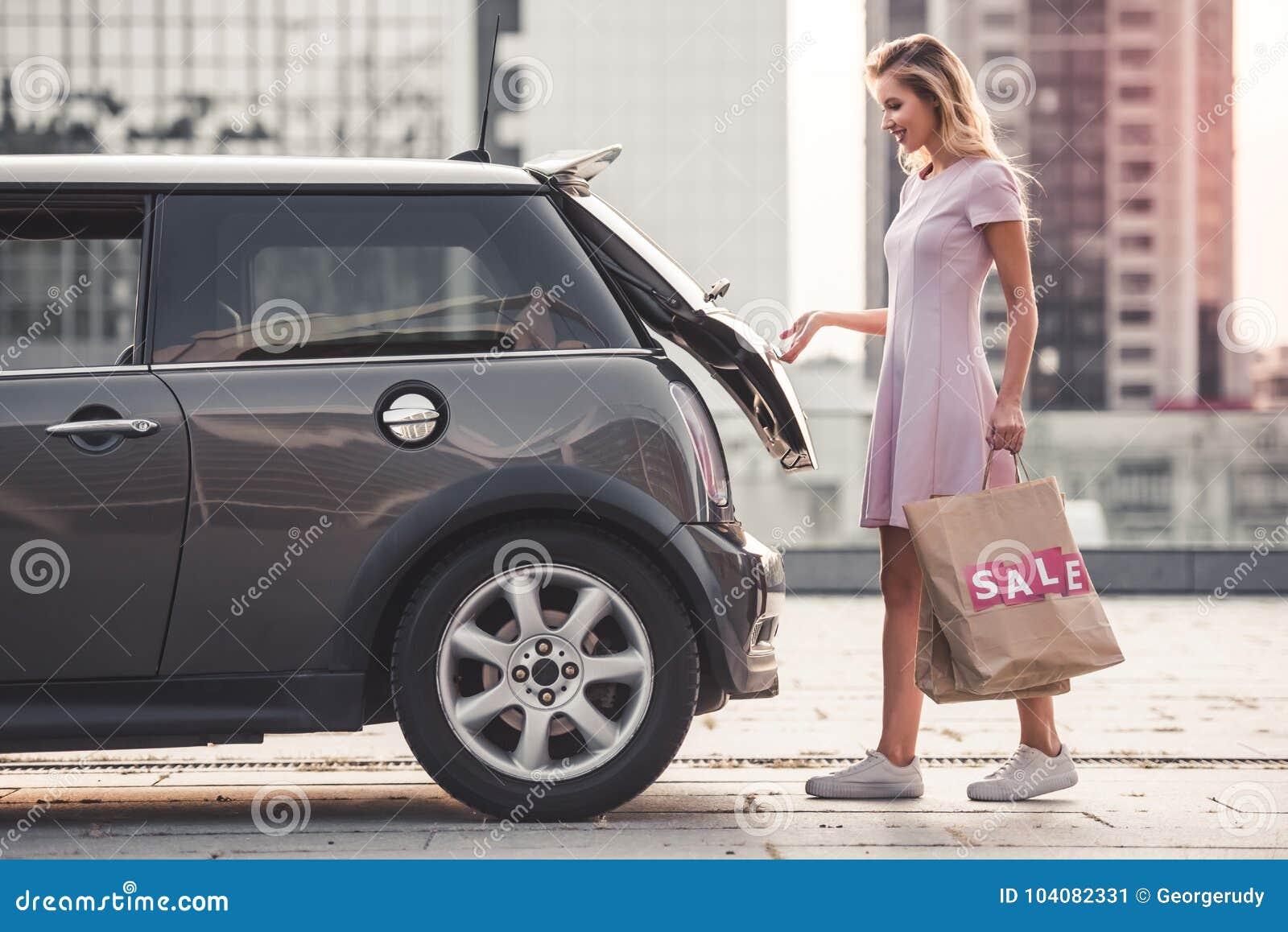 Menina loura perto do carro
