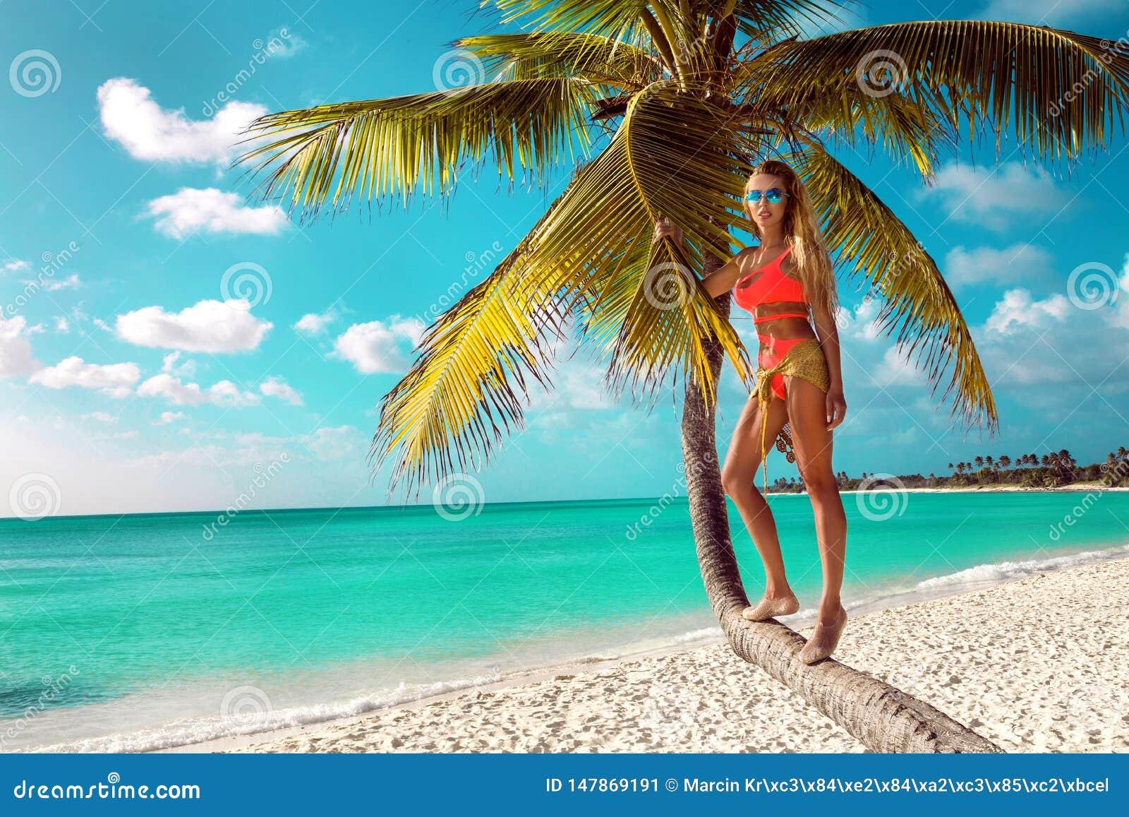 Menina loura  sexy  na praia com palmas e o c?u azul