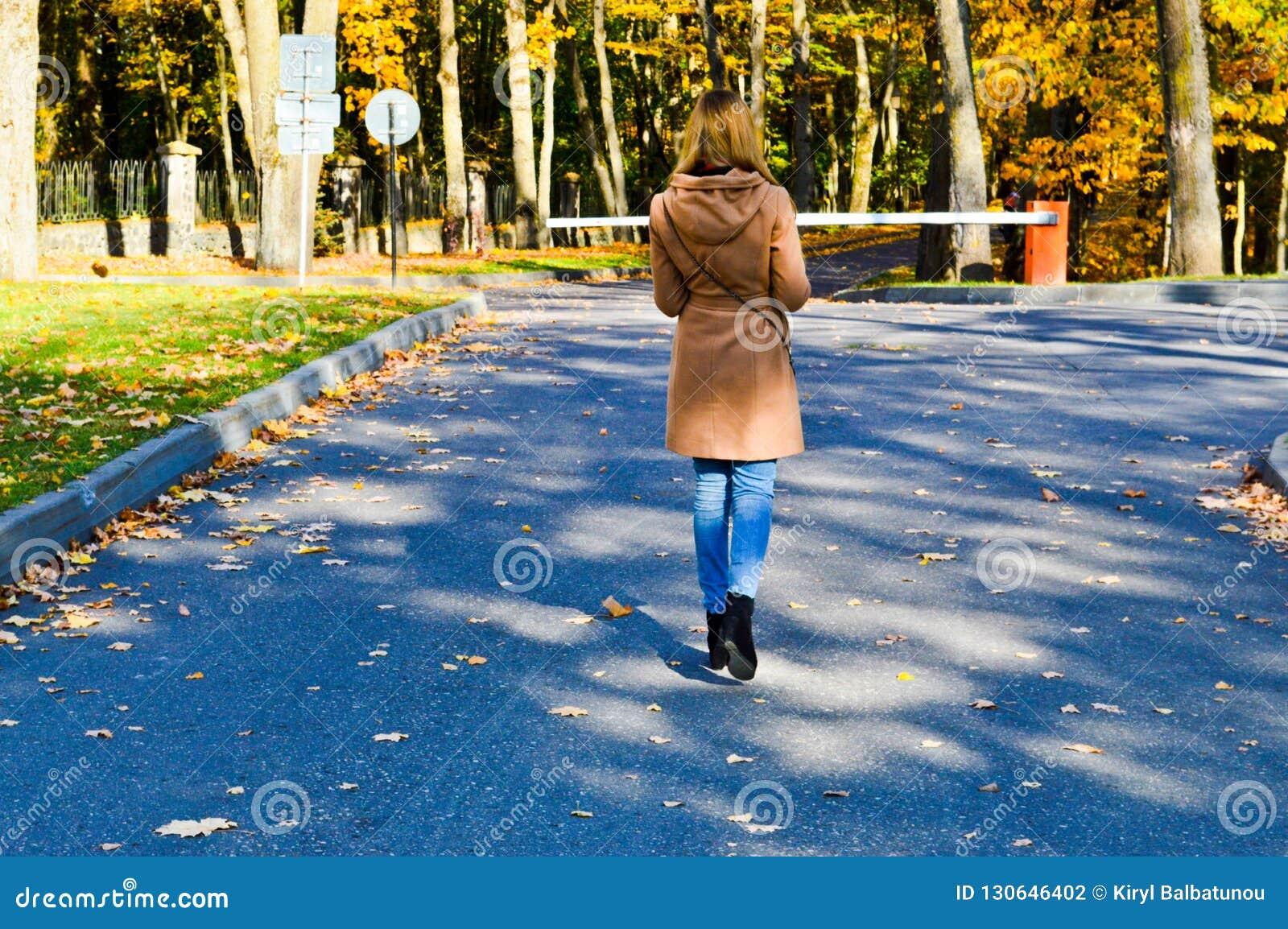 Menina magro fina bonita nova, uma mulher em um revestimento marrom com caminhadas longas do cabelo no parque do outono com folha