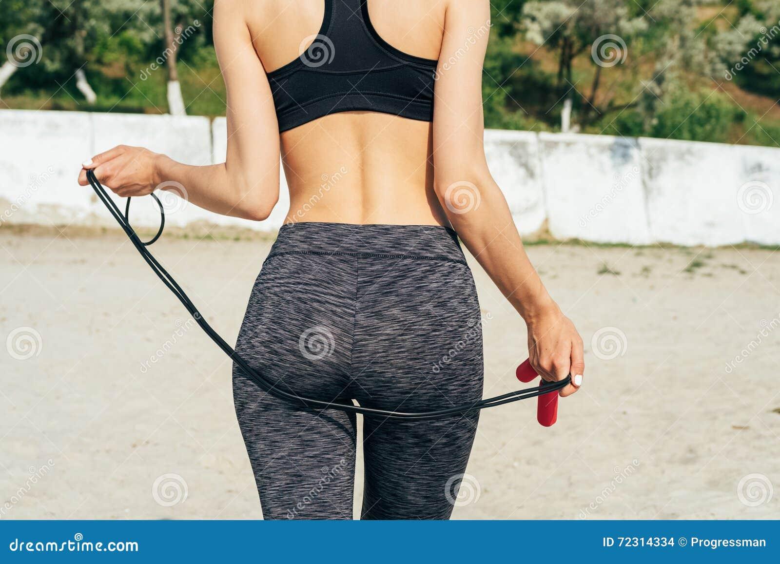 Menina magro no sportswear na praia que guarda uma corda de salto vermelha