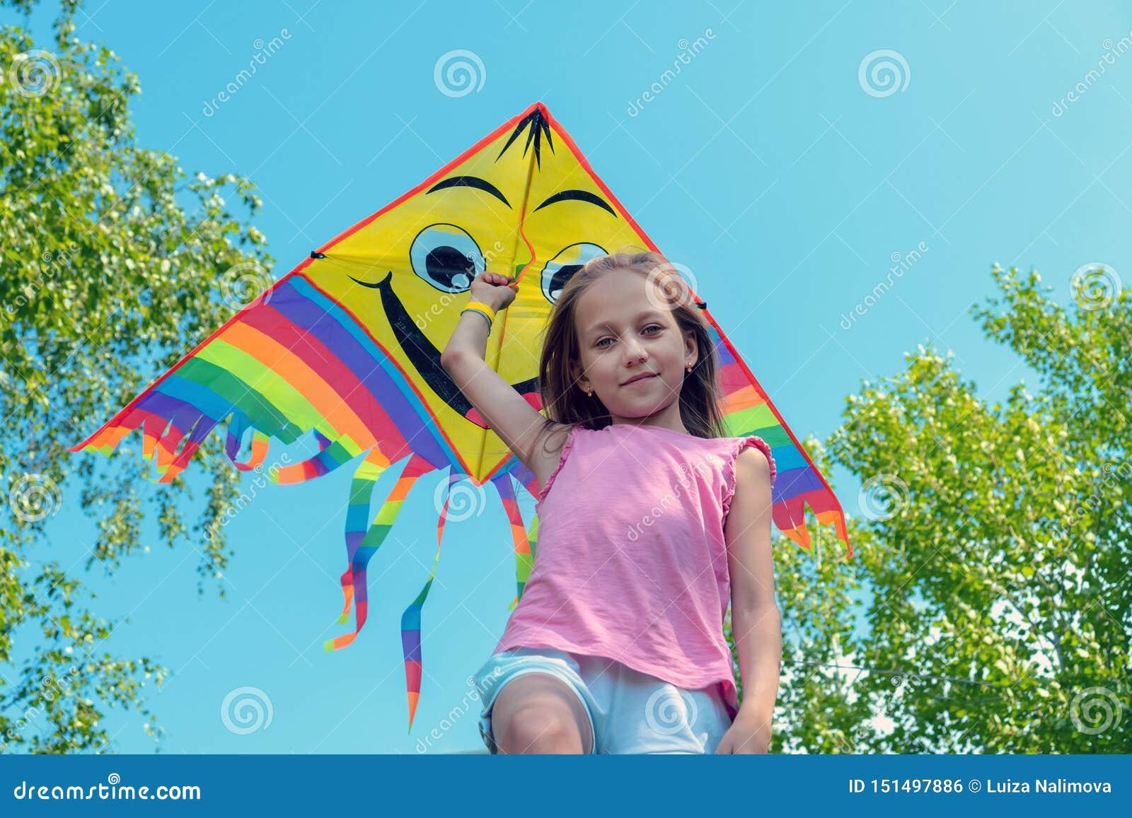 A menina mantém um papagaio brilhante em seus mãos e sorrisos contra o céu azul Conceito do verão, da liberdade e da infância fel