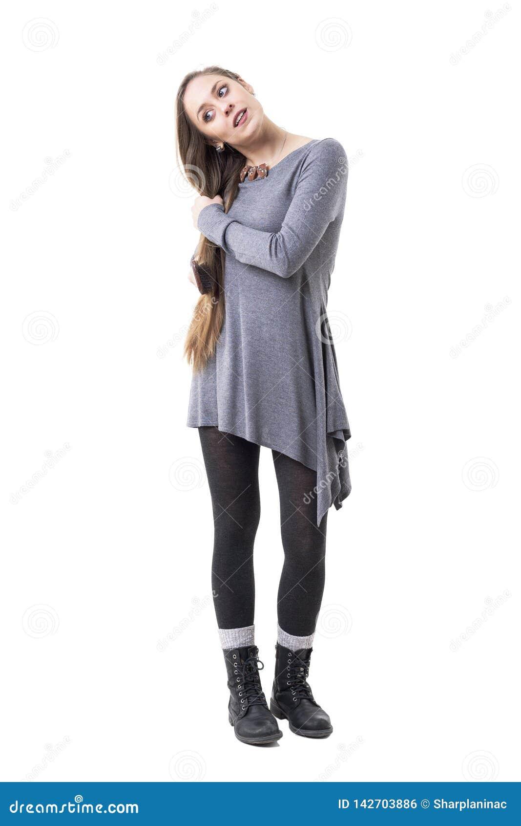 Menina milenar nova à moda que olha para baixo ao escovar seu cabelo louro longo com escova de cabelo