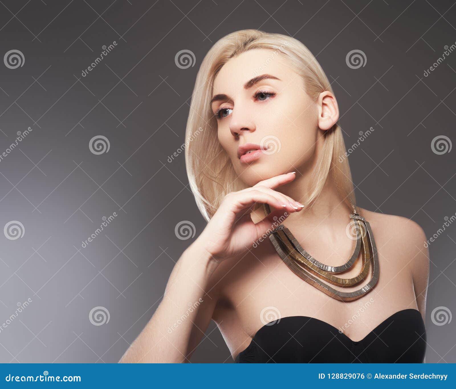 Menina modelo bonita com tratamento de mãos metálico cor-de-rosa em pregos Composição e cosméticos da forma
