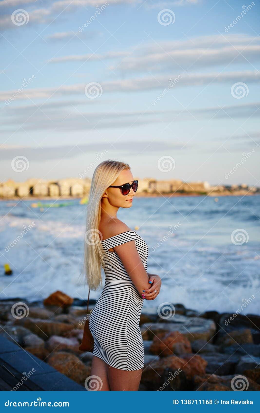 Menina modelo loura bonita e elegante com corpo  sexy  no vestido curto listrado na moda e em óculos de sol à moda