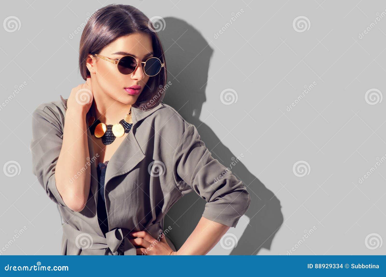 A menina modelo moreno da beleza com composição perfeita, os acessórios na moda e a forma vestem