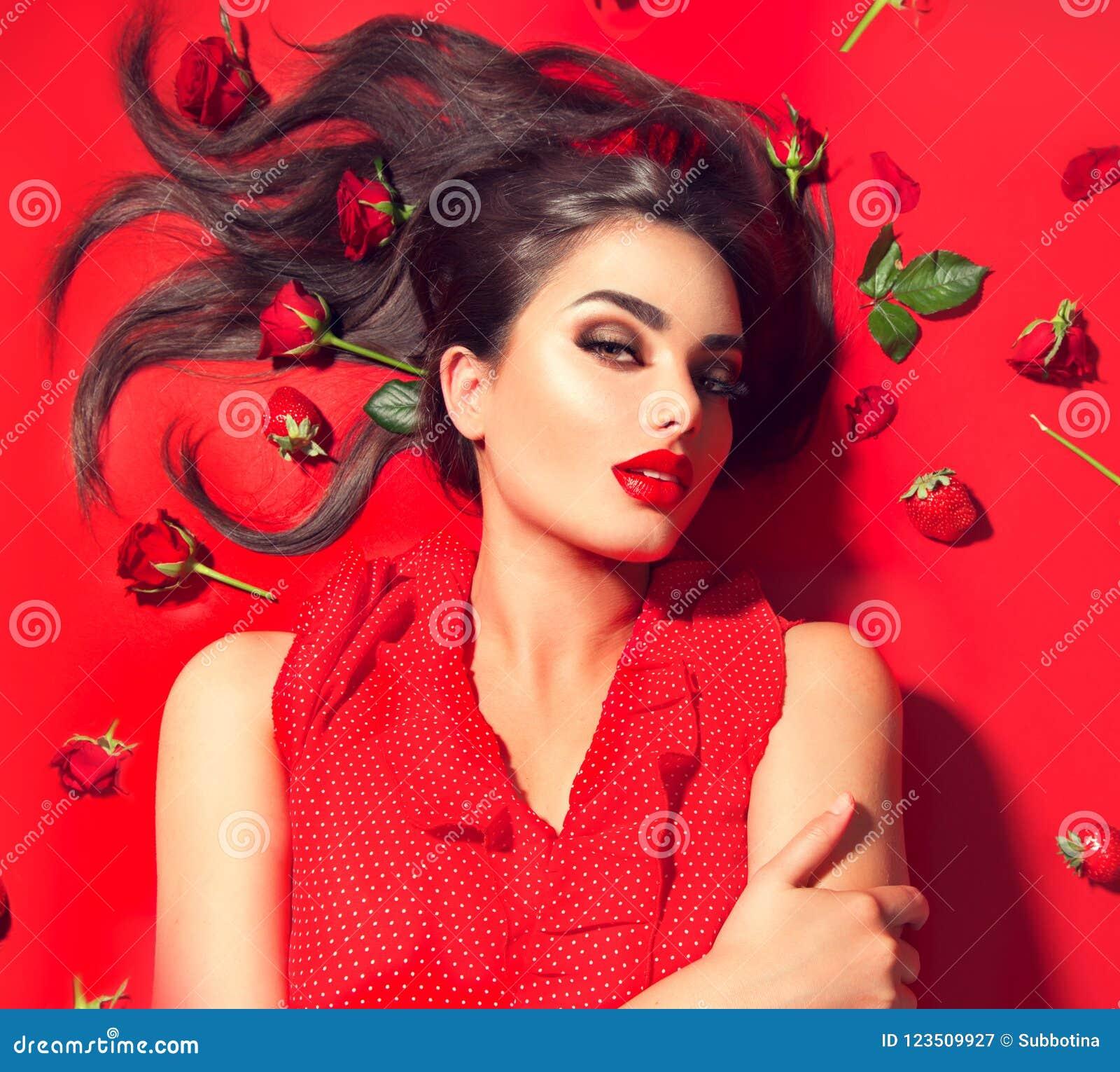 Menina modelo  sexy  da beleza que encontra-se no fundo vermelho com flores e as morangos cor-de-rosa Jovem mulher moreno bonita