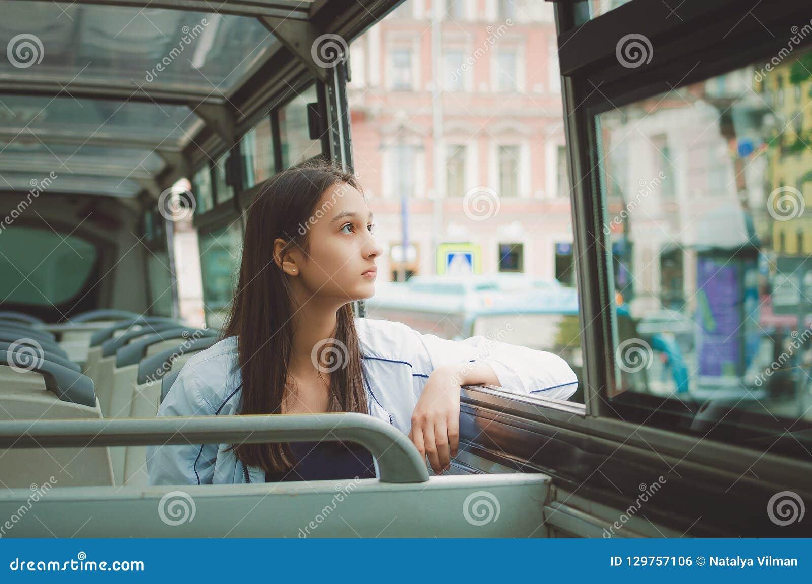 A menina monta no ônibus de excursão e olha para fora a janela St Petersburg, Rússia