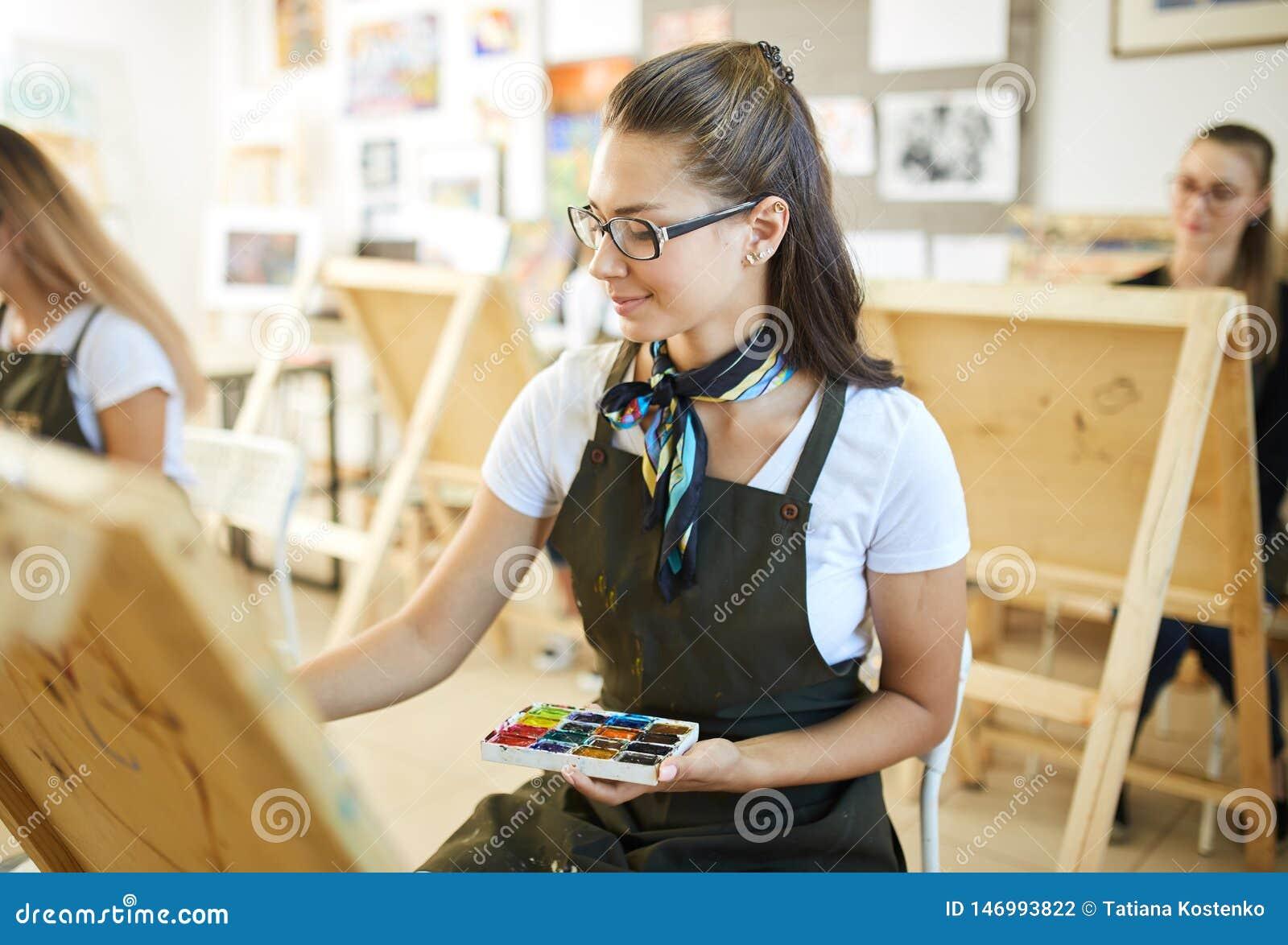Menina moreno bonita nos vidros vestidos no t-shirt branco e no avental marrom com um lenço em torno de suas pinturas a do pescoç