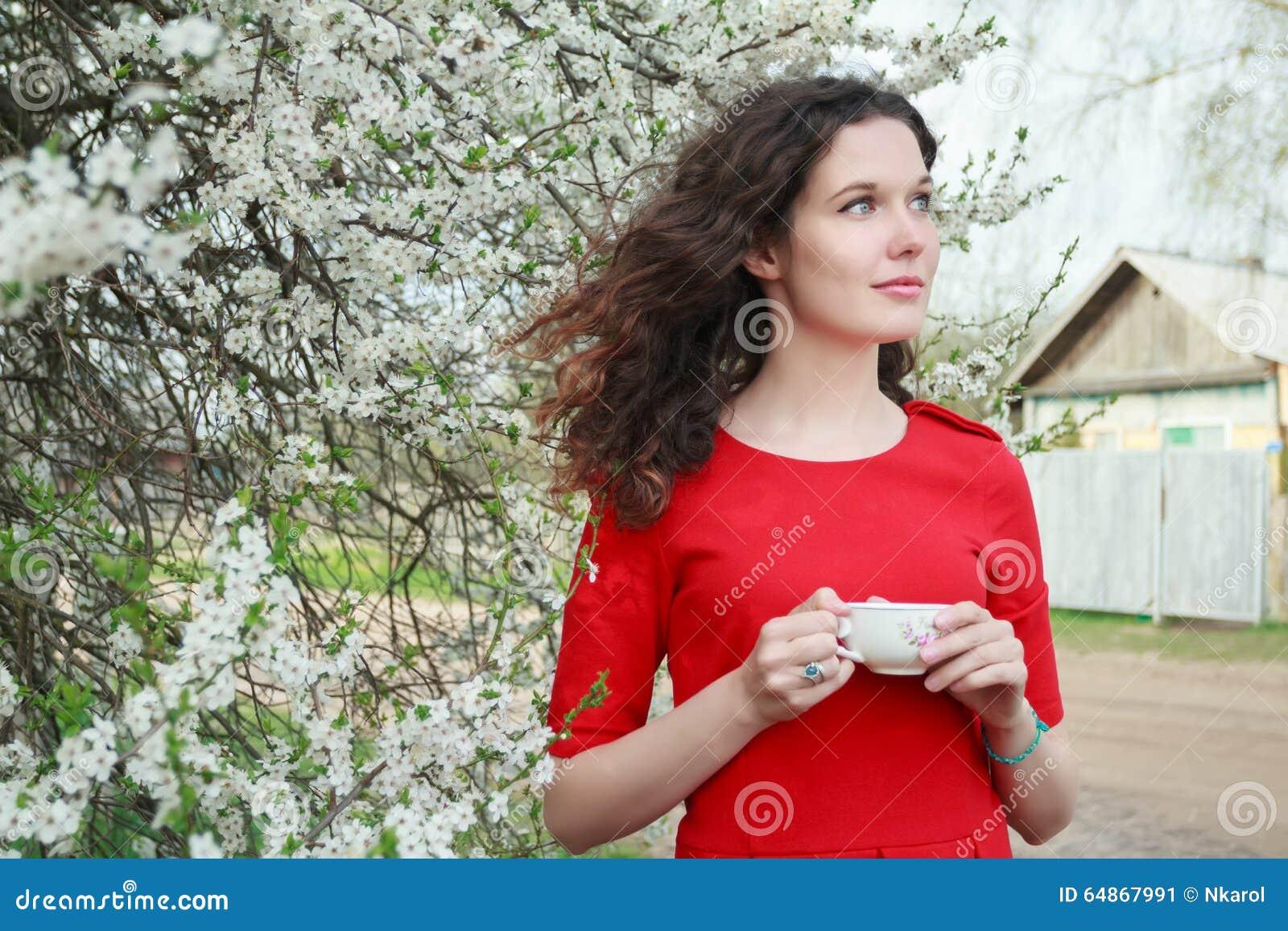 Menina moreno bonita nova com o copo de chá no braço que está no jardim de florescência da mola