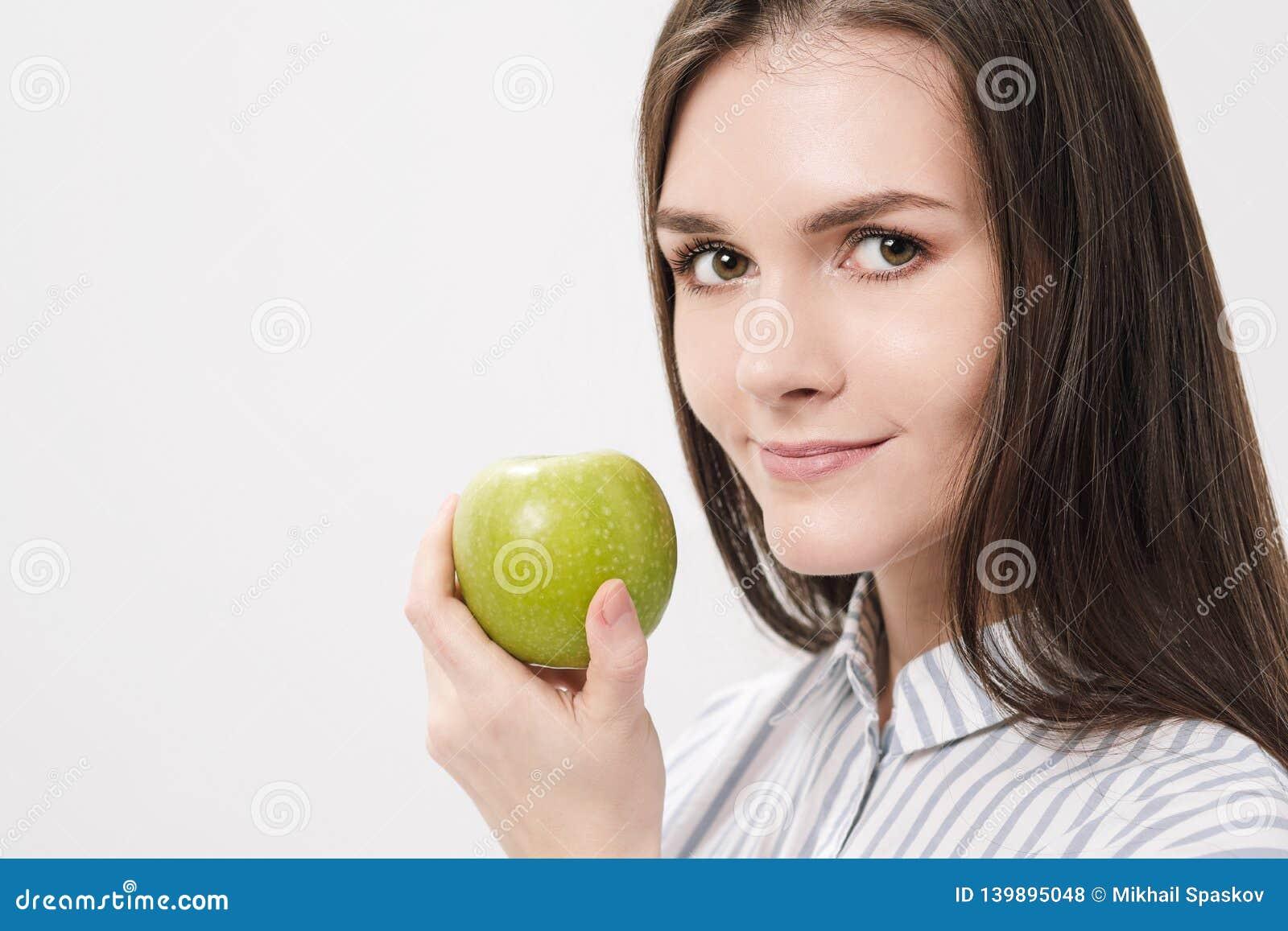 Menina moreno bonita nova em um fundo branco que guarda uma maçã verde fresca