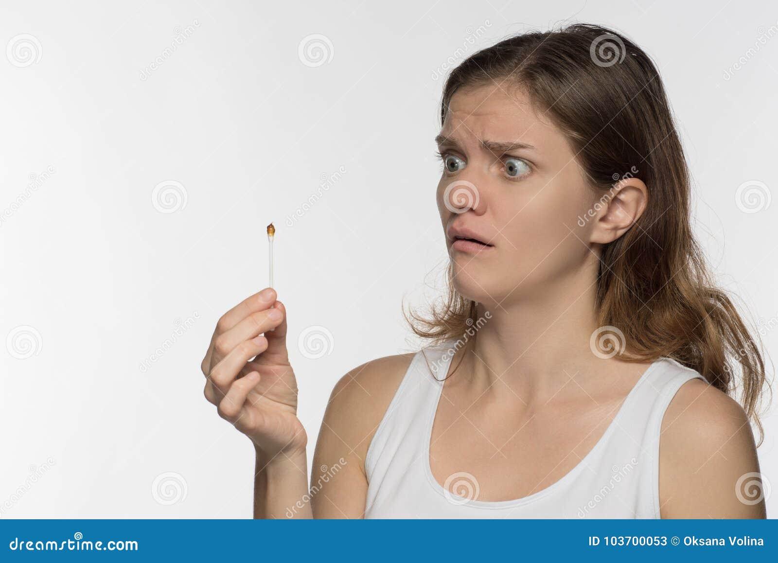 A menina moreno bonita nova limpa as orelhas com os wi dos hashis