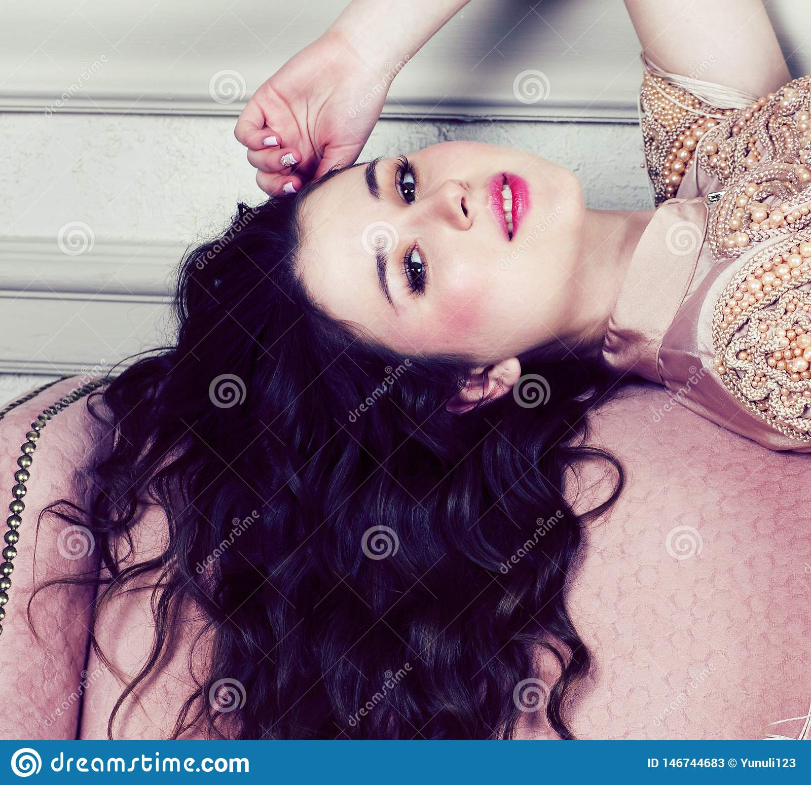 Menina moreno bonita nova no vestido da forma no sof? que levanta no interior luxuoso, conceito rico dos povos do estilo de vida