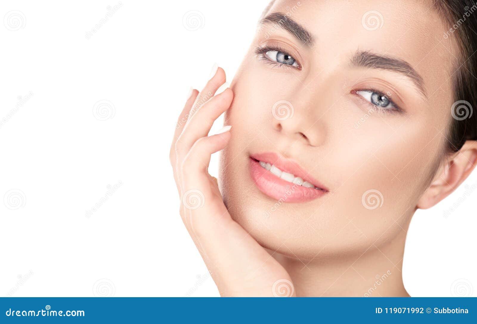Menina moreno bonita que toca em sua cara Pele fresca perfeita Retrato da beleza isolado no fundo branco Juventude e skincare co