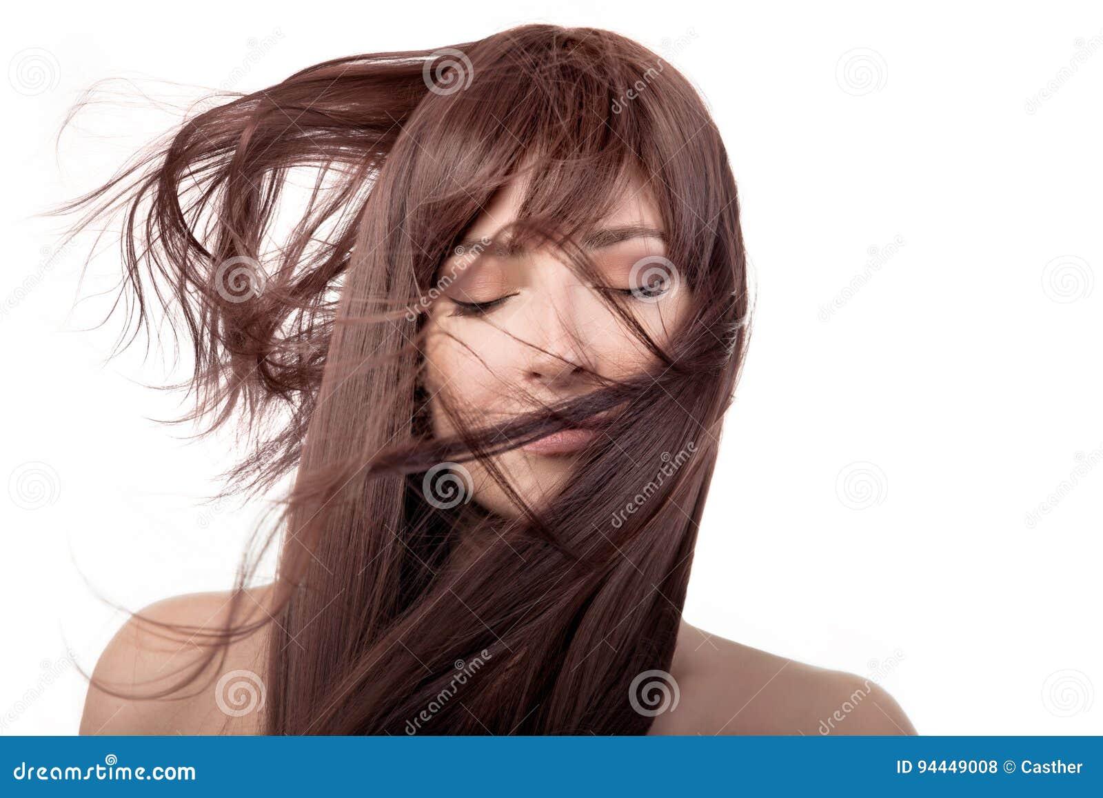 Menina moreno da beleza Cabelo longo saudável que voa sobre a cara